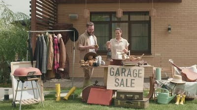 Couple Preparing for Garage Sale and Posing