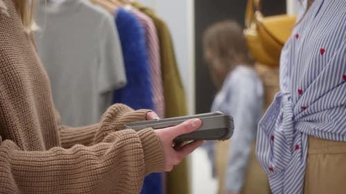 Closeup of Woman Making Payment By Card in Showroom Fashion Clothes Store for Brand New Shirt and