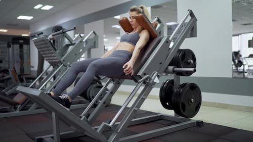 Fit woman practicing back squats in exercise machine