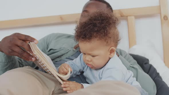 Thumbnail for Man and Toddler Reading Book in Bed