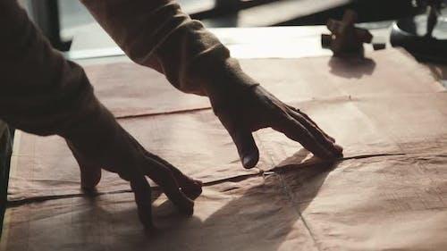 Männerhände bewegen sich nach den Blaupausen, alte dekrepit Dokumente