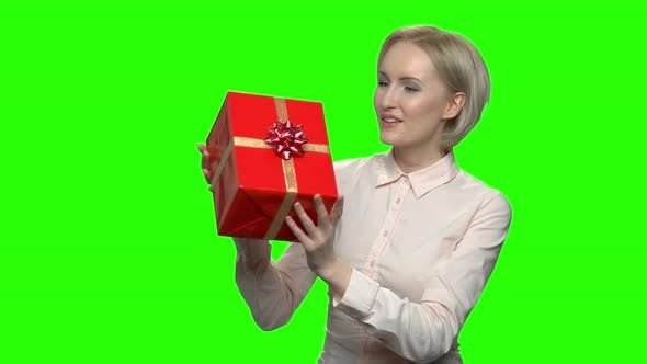 Woman Shaking Gift Box with Excitement