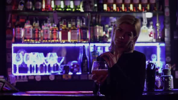 Thumbnail for Beautiful Girl with Blond Hair Standing Near the Bar Counter on the Background of Flickering Light
