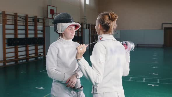Thumbnail for Two Young Women Fencers in White Protective Suits Standing on Front of Each Other and Having