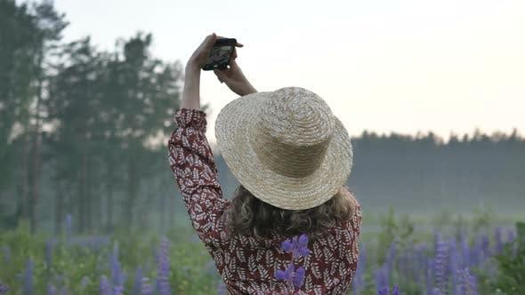 Happy Lady in Strohhut macht Selfie in Lupine Blumen Feld