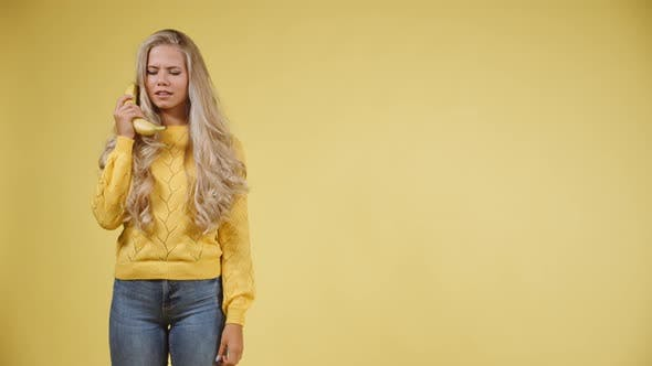 Thumbnail for Goofy Blonde Model Holding a Banana on Her Ears As If Talking To Someone