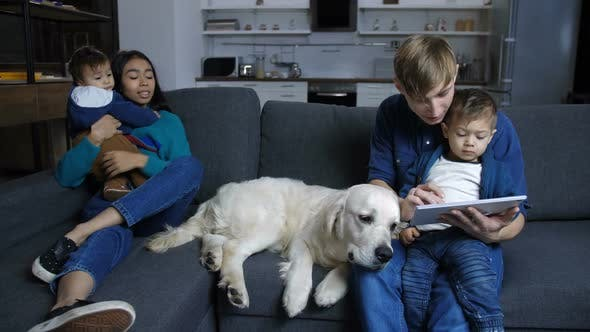 Thumbnail for Family Sitting on Couch with Pet Labrador at Home