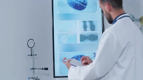 Handheld Shot of Doctor in His Modern Research Center Taking Notes on a Clipboard