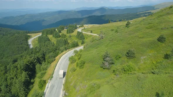 Thumbnail for White Truck Going Down a Mountain Road with Panoramic View of Hills
