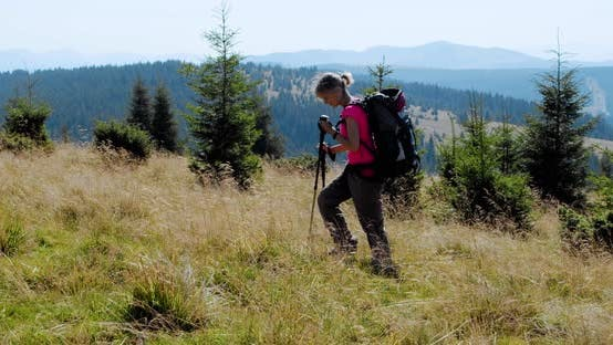 Cover Image for Woman Hiking in Mountains with Backpack, Enjoying Her Adventure. Slow Motion V3