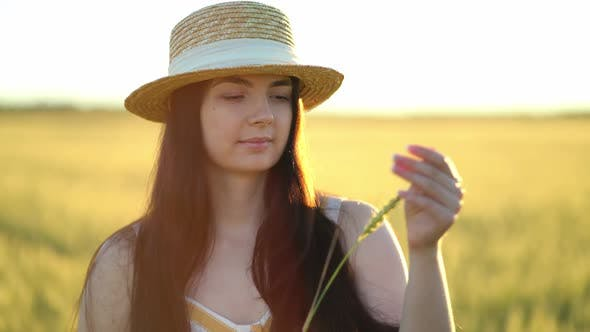 Thumbnail for Beautiful Young Woman with a Hat Holds an Ear of Wheat in Her Hands