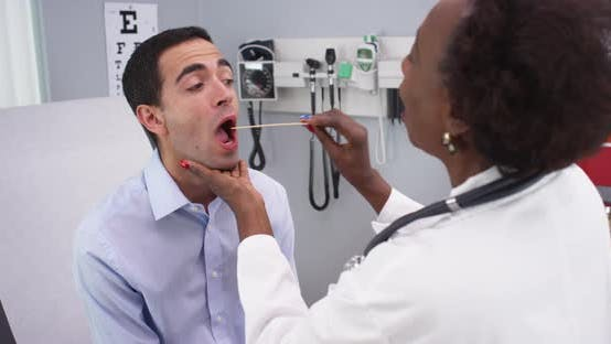 Thumbnail for Charming senior black doctor checking young patients throat for swollen illness