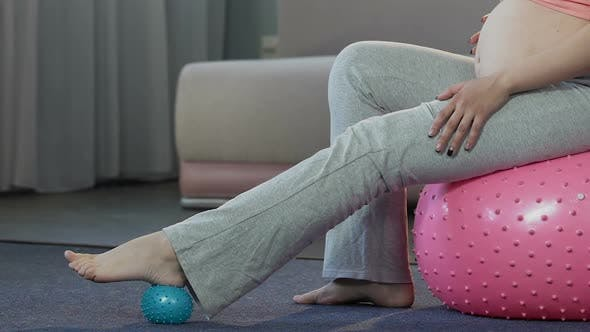 Thumbnail for Mother-To-Be Sitting on Fitness Ball, Massaging Feet With Rubber Ball, Body Care