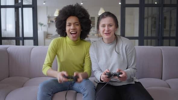 Porträt junger freudiger Spielerinnen, die Highfive geben, das Multiplayer-Videospiel spielt