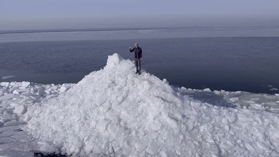Thumbnail for Aerial Dron View of Young Active Happy Man Staying on the Ice Glaciers Near Coastline of Winter Sea