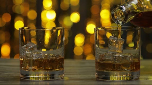 Pouring of Whiskey, Cognac or Brandy From Bottle Into Glasses with Ice Cubes. Shiny Background