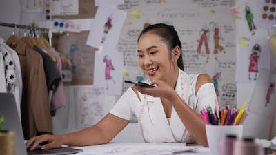 Woman fashion designer talking on mobile phone with customer