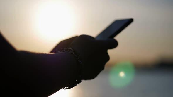 Close up Asian woman hand using smartphone beside bars sunset.