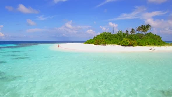 Thumbnail for Aerial view of a man walking on the beach around a tiny deserted tropical island