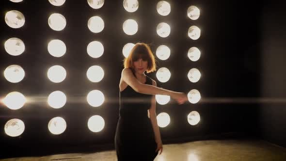 Thumbnail for Beautiful woman dancing in front of a wall of lights