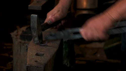Blacksmith in Forge Beats Hot Metal on Anvil with Hammer