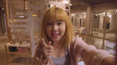 Asian friendly women influencer waving hand looking at camera at night cafe.