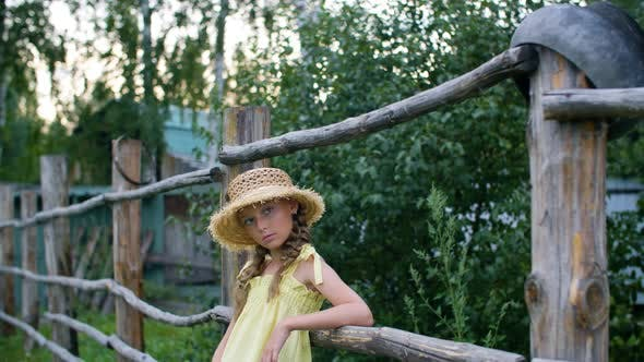 Thumbnail for Country Girl in Straw Hat with Two Braids Leaning on Wooden Fence in Summer Village. Portrait Teen