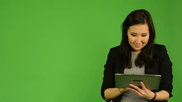 Cover Image for Young Attractive Asian Woman Works on Tablet and Smiles - Green Screen Studio