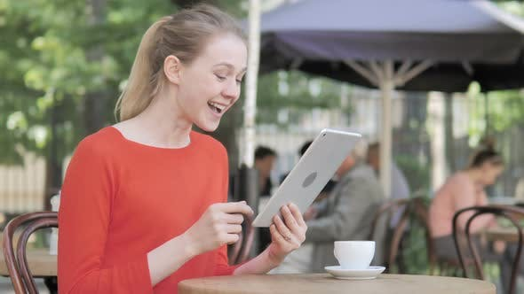 Thumbnail for Young Woman Celebrating Win on Tablet, Sitting in Cafe Terrace