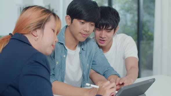 Asian Gay lgbtq men couple sign contract on tablet at home.