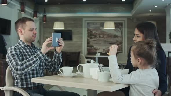 Thumbnail for Happy Father Taking Photo of His Wife Kissing Their Daughter By Smartphone at Restaurant.