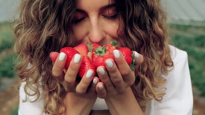 Smiling Young Woman Smelling Strawberries Scent at Greenhouse