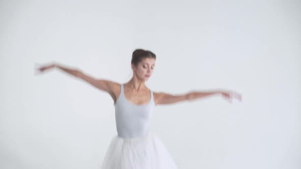 Elegant Woman in a White Tutu Dance Ballet and Perform Choreographic Elements on a White Background