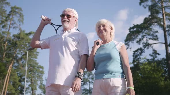 Thumbnail for Mature Couple in Sunglasses and Tennis Rackets Standing on a Tennis Court in the Sun