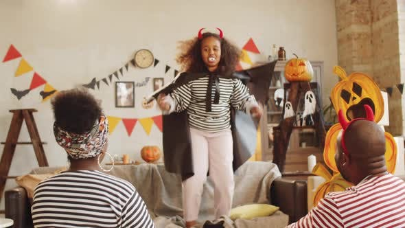 Thumbnail for Black Girl in Vampire Costume Giving Halloween Performance to Parents