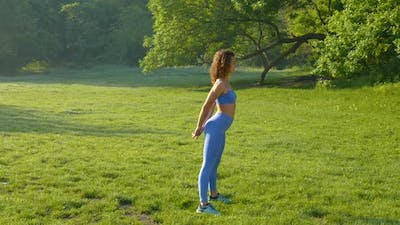 A Young Woman is Engaged in Fitness at Nature