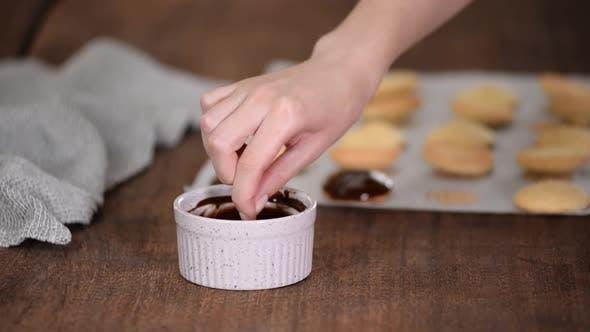 Chefin dekoriert Plätzchen mit geschmolzener Schokolade