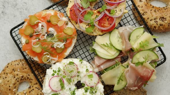 Köstliche Bagel Sandwiches mit cremigem Käse, Schinken, Hummus, Lachs und Gemüse