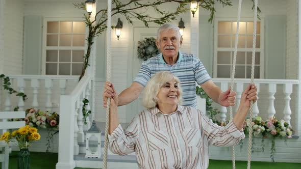 Thumbnail for Senior Couple Together in Front Yard at Home. Man Swinging Woman. Happy Mature Retired Family