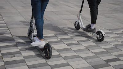 A Man and a Woman Ride Electric Scooters