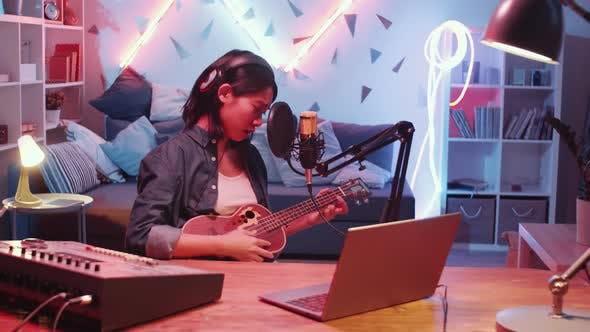 Thumbnail for Asian Female Singer Playing Guitar and Singing in Home Recording Studio