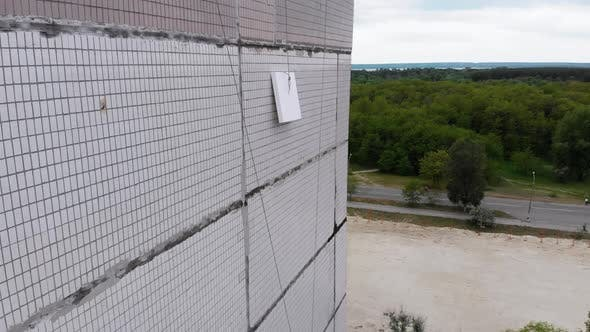 Thumbnail for Aerial View on Styrofoam Block Feed on Rope To Industrial Climber Warming Facade