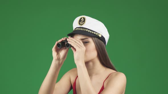 Thumbnail for Young Woman in a Sailor Cap Looking Away with Binoculars Smiling Joyfully