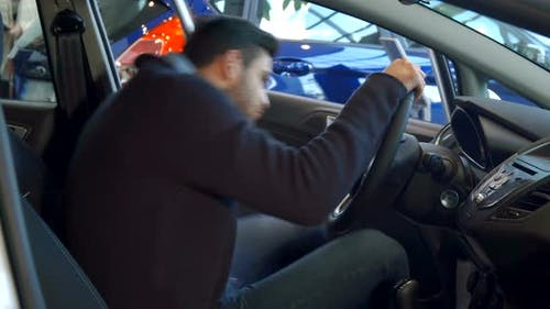 Man Fastens His Seat Belt in the Car