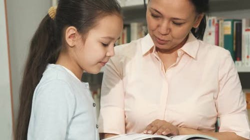 Mother and Daughter Choosing Books at the Library or Bookstore