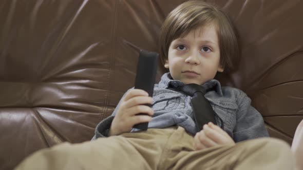 Thumbnail for Portrait Adorable Small Boy Sitting on the Leather Sofa with Legs Apart Changing Channels on TV
