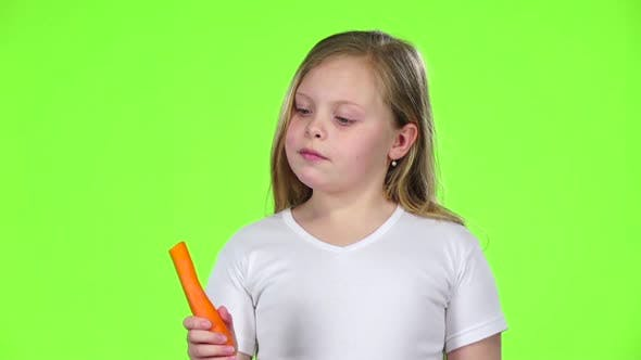 Thumbnail for Little Girl Bites a Carrot, It Is Healthy. Green Screen. Slow Motion