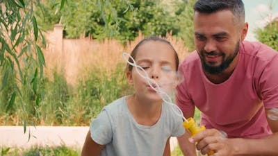 Father And Daughter Making Soap Bubbles Outdoors