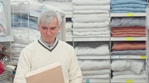 Senior Man Shopping for Bedroom Textile at Furnishings Store