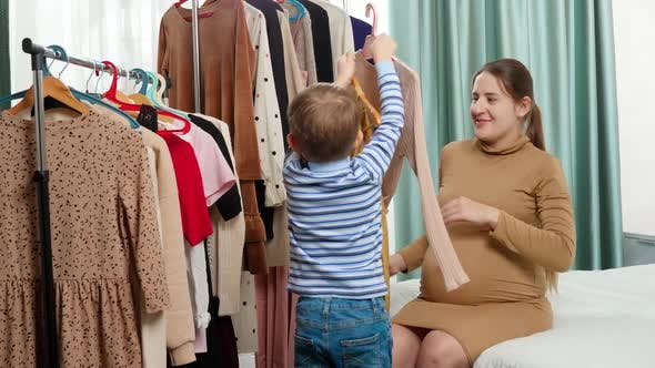 Little Toddler Boy Helping His Mother Choosing Clothes To Wear in Wardrobe at Bedroom